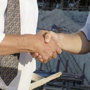 Two Men Wearing Hard Hats Shaking Hands, on a Building Site
